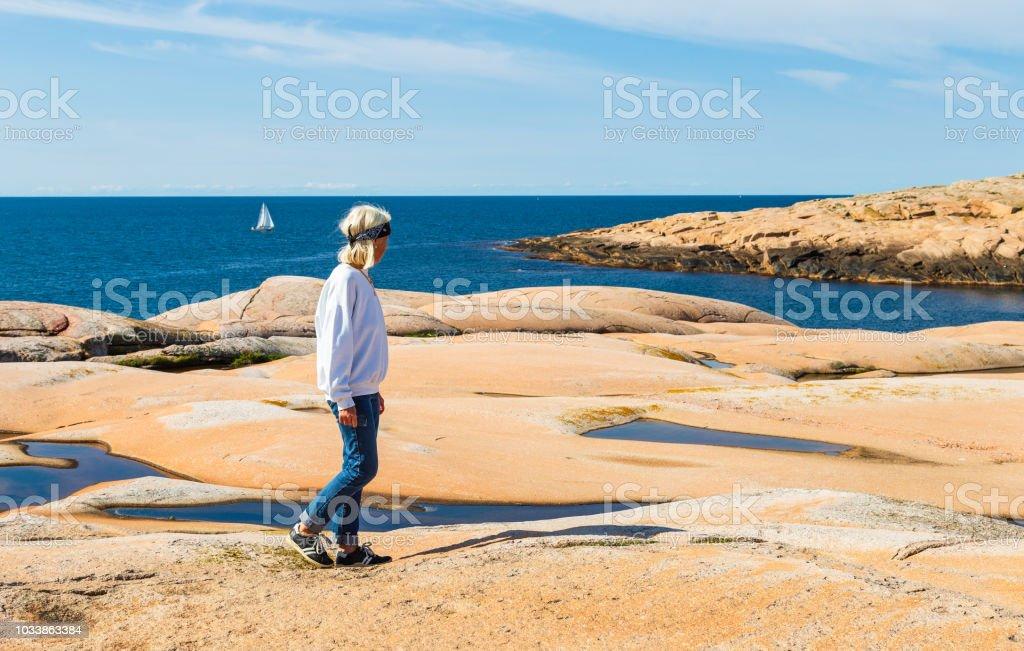 Senior woman on Hållö island, Bohuslän, near Smögen on the Swedish west coast - admiring the beautiful rock formations against the blue ocean stock photo