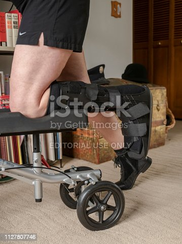 Beaverton, Oregon, USA -  February  04, 2019: A senior woman on a knee scooter with a walking boot, also Called a CAM boot. She is moving around the bedroom on the knee walker to protect a fractured ankle. This is a bedroom in a home in Beaverton, Oregon.