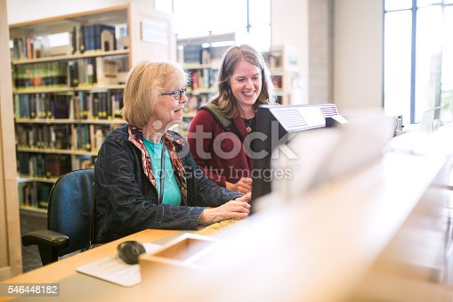 A young adult woman assists a mature woman in her 60's as she uses a public computer at the library to do some internet research.  They smile as they discuss how to use the technology for things like email or other online tools.
