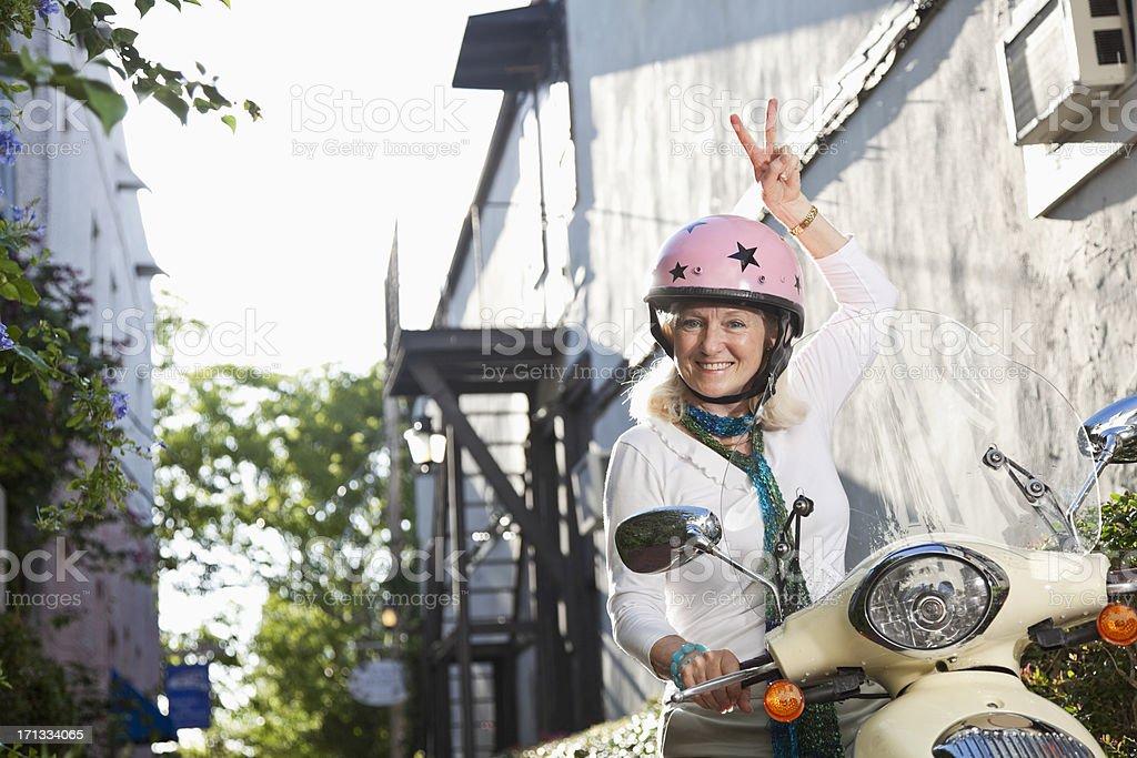 Senior woman on motor scooter stock photo