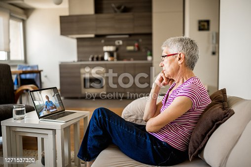 Senior woman on online therapy. She is sitting on the sofa in her living room, having a video call