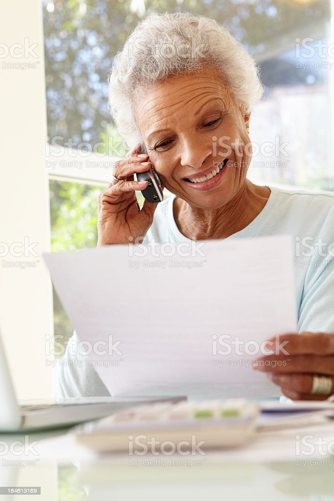 Senior Woman On Phone Using Laptop At Home royalty-free stock photo