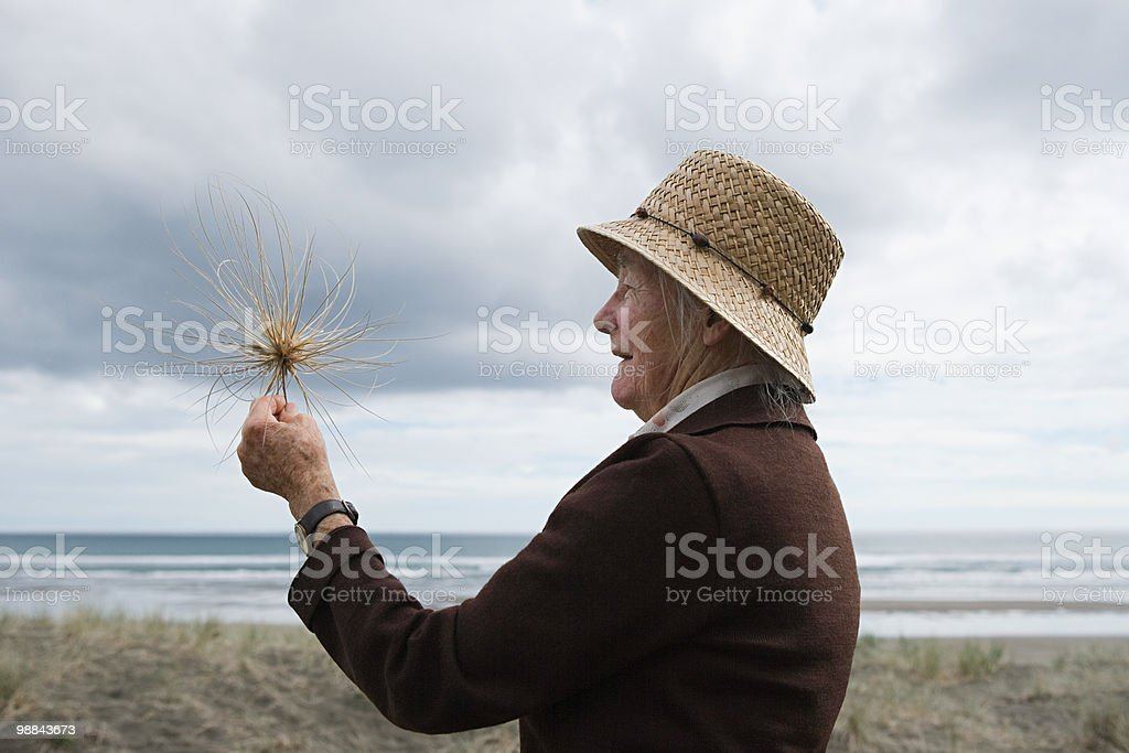 Senior woman on Piha Beach, Auckland royalty free stockfoto