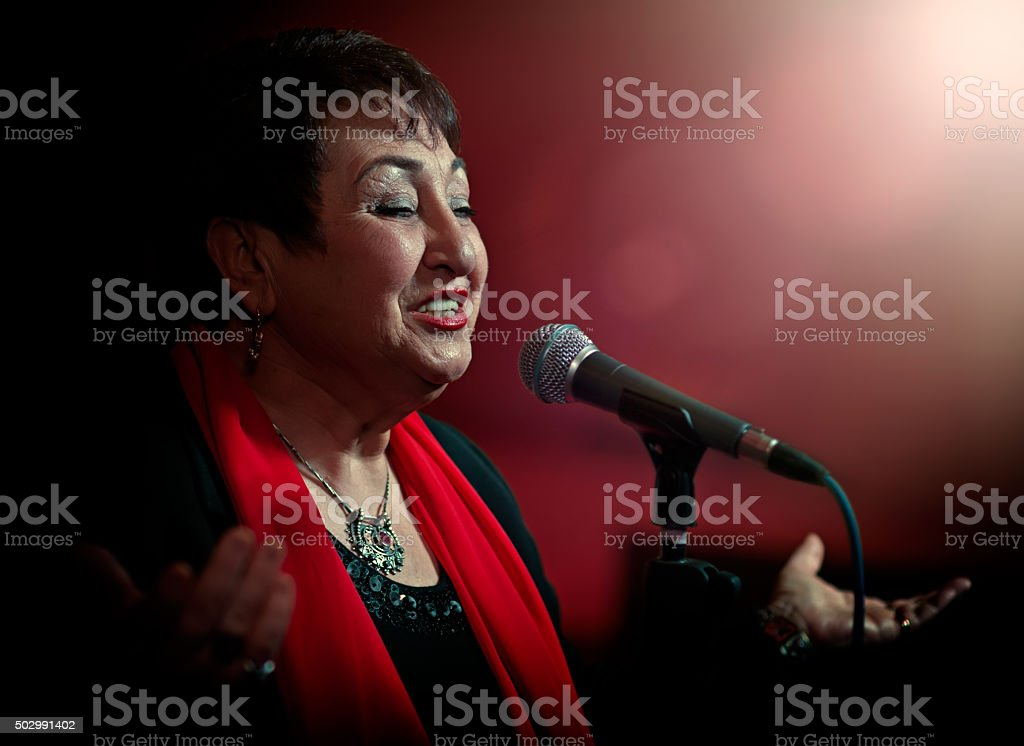 Senior woman on stage with a microphone
