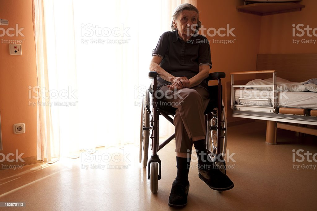 Senior Woman on Wheelchair in a Nursing Home Room royalty-free stock photo