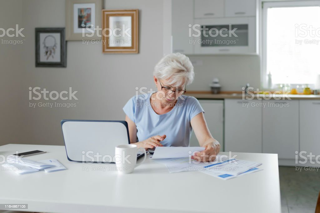 Serious Frustrated Middle Aged Senior Woman Worried Reading Bad News...