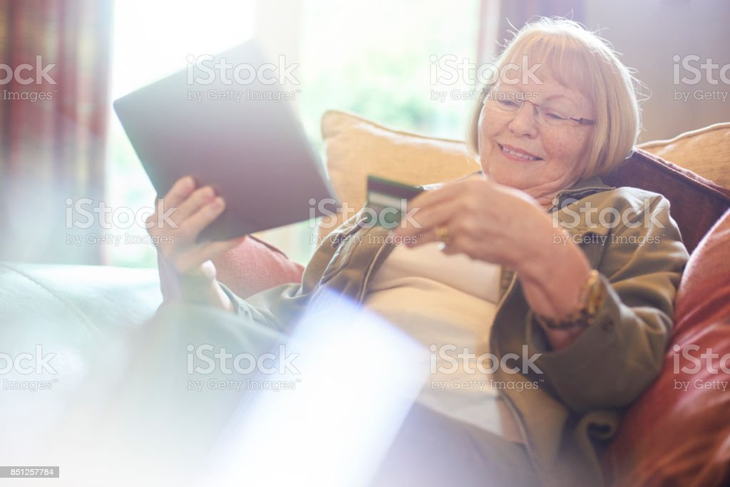 senior woman online shopping with digital tablet stock photo