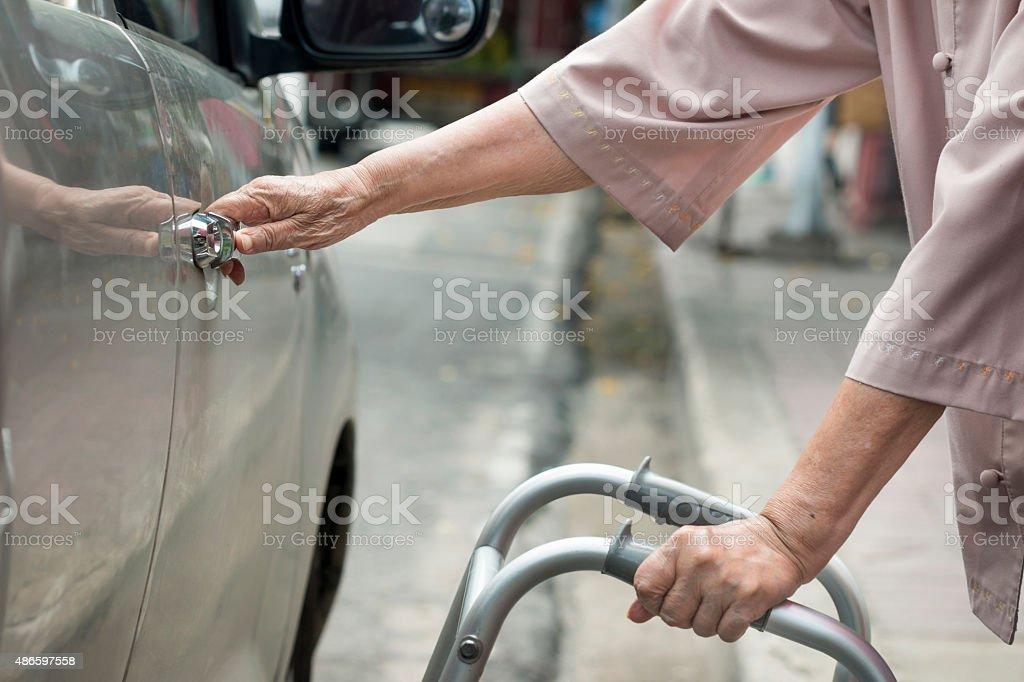 senior Frau öffnen Tür mit walker Auto auf der Straße. – Foto