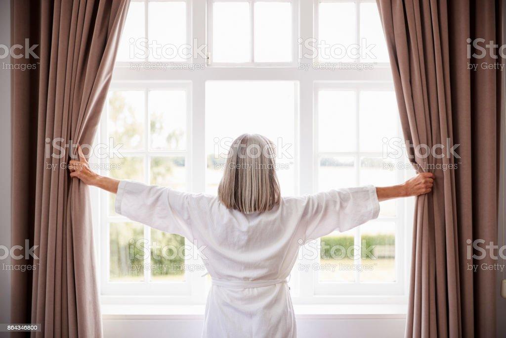 Ältere Frau Schlafzimmer Vorhänge zu öffnen und auf der Suche von Fenster – Foto