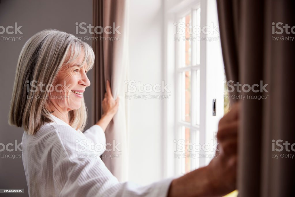 Senior Woman Opening Bedroom Curtains And Looking Out Of Window - Royalty-free 60-69 Years Stock Photo