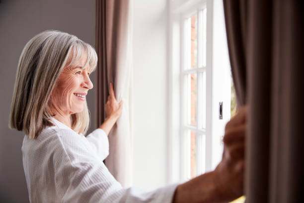 senior woman opening bedroom curtains and looking out of window - senior home stock photos and pictures