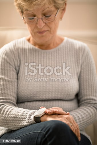 Senior woman holding her new panic button health alarm. She is relaxed and confident while she has this useful device