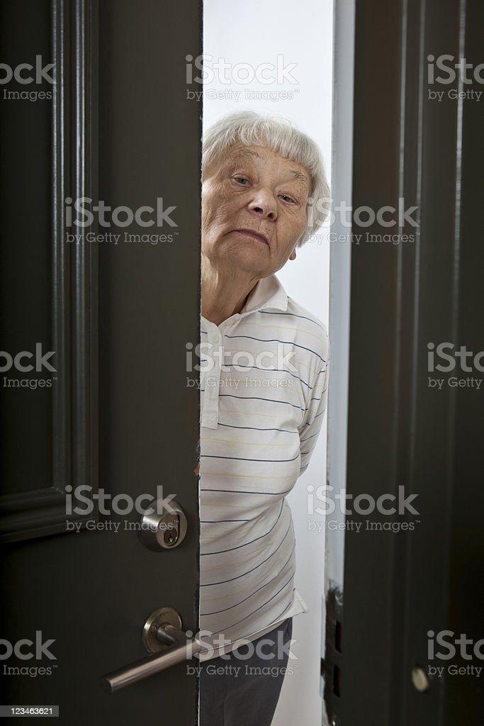 Senior Woman opening door to a stranger or salesman stock photo