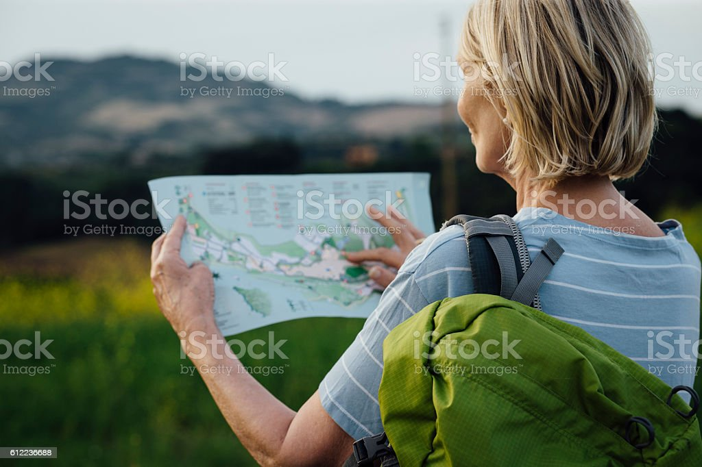Senior Woman Outdoors with a Map and Backpack stock photo
