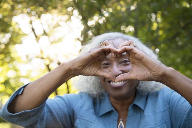 Senior Woman Outside Making 'Heart' stock photo