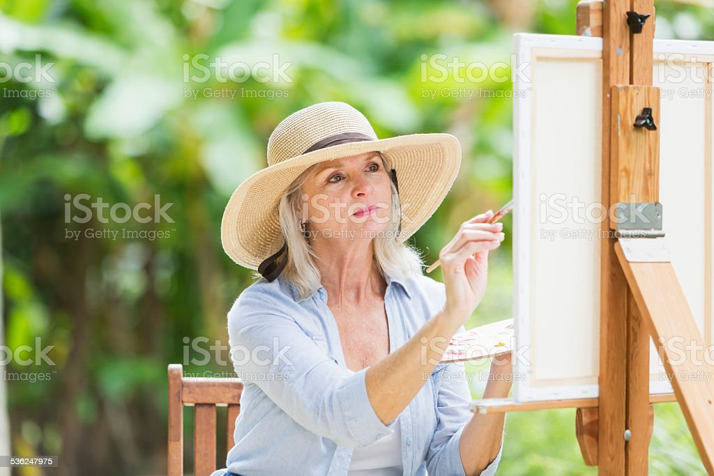 Senior woman painting a picture on canvas stock photo