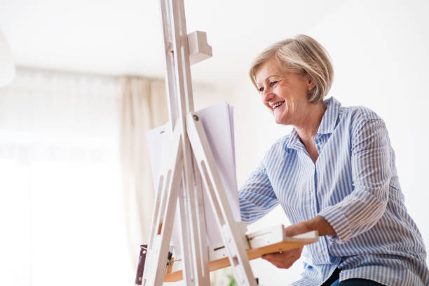 A senior woman painting at home. stock photo