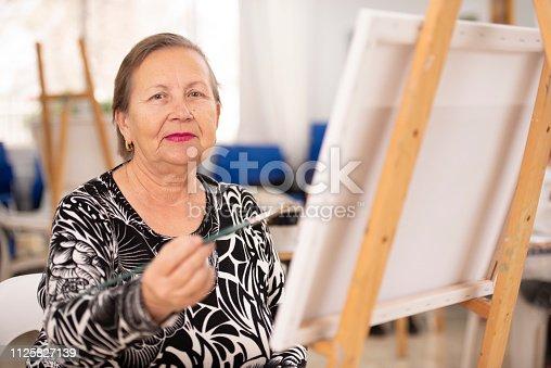 585509074 istock photo Senior woman painting on canvas. 1125827139