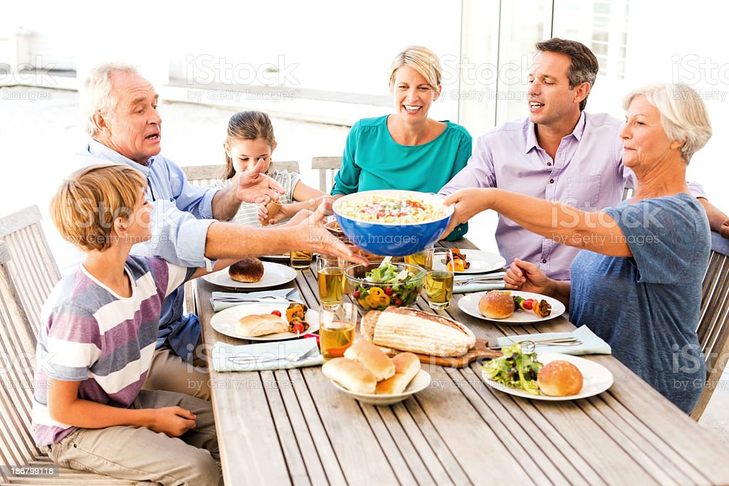 Senior Woman Passing Food While Having Lunch With Family Outdoor royalty-free stock photo