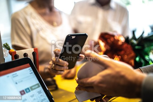 Senior woman paying by mobile in a store