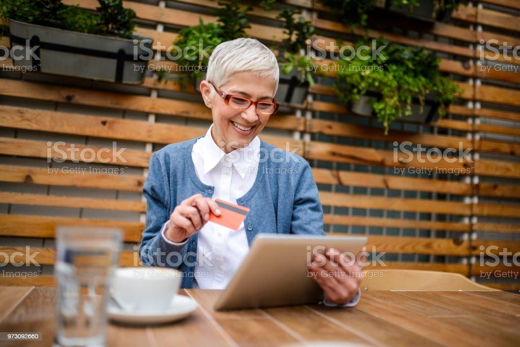 Senior woman paying online. stock photo