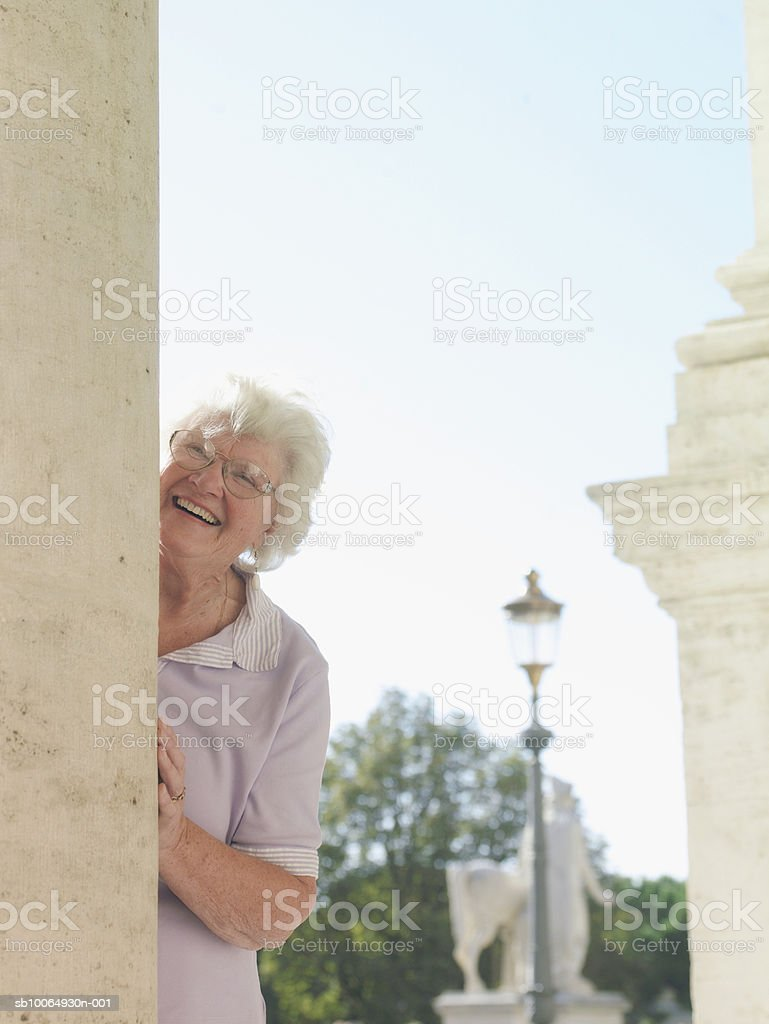 Senior woman peeking through wall, smiling foto de stock libre de derechos