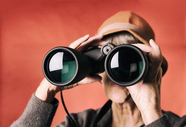 Senior woman peers curiously through binoculars, stock photo