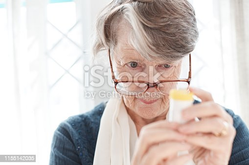 istock Senior woman peers, trying to read instructions on medication 1155142035