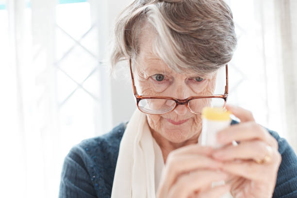 Senior woman peers, trying to read instructions on medication stock photo