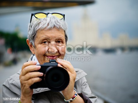 Senior woman photographer with camera  in Moscow, Russia