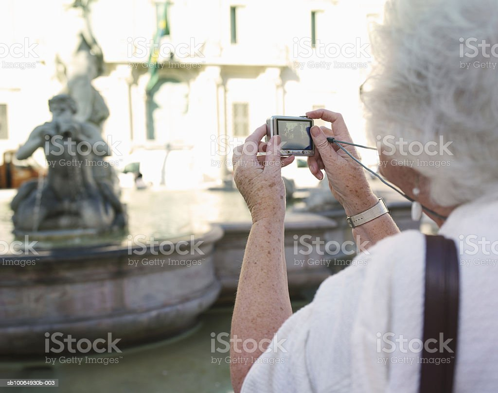 Senior woman photographing fountain (focus on foreground) royalty-free stock photo