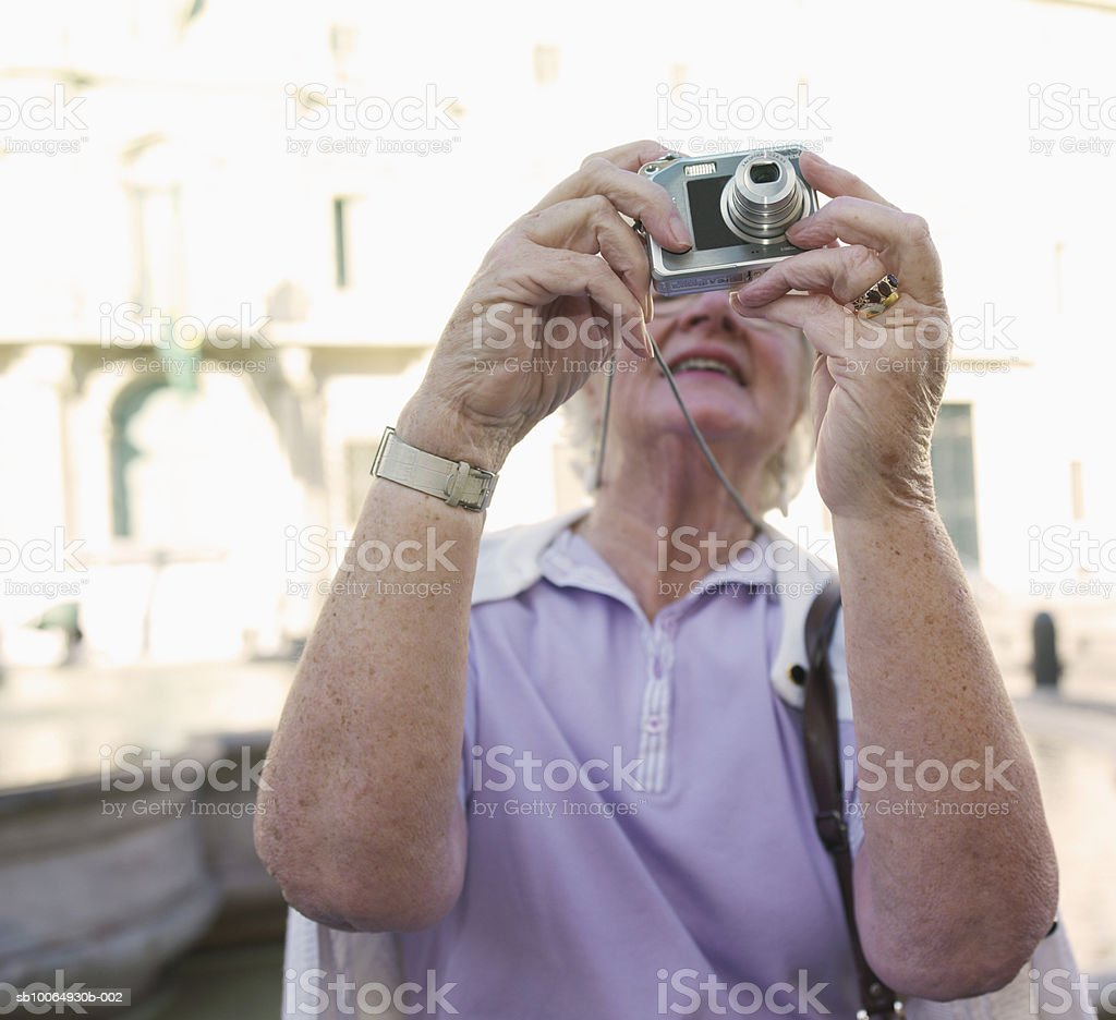 Senior woman photographing (focus on foreground) royalty free stockfoto