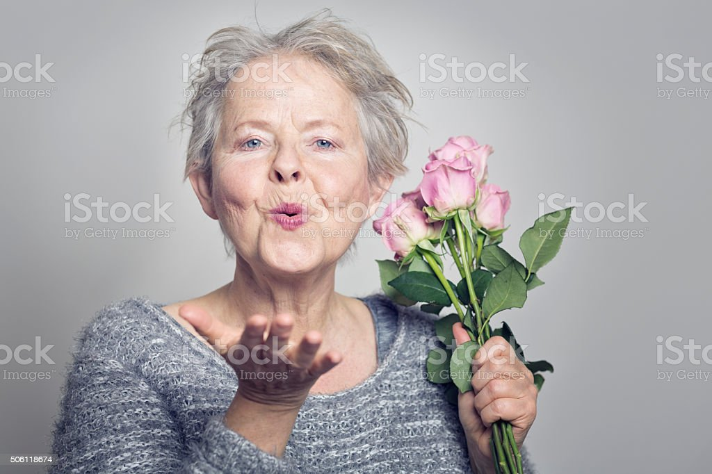 senior woman pink roses blowing a kiss stock photo