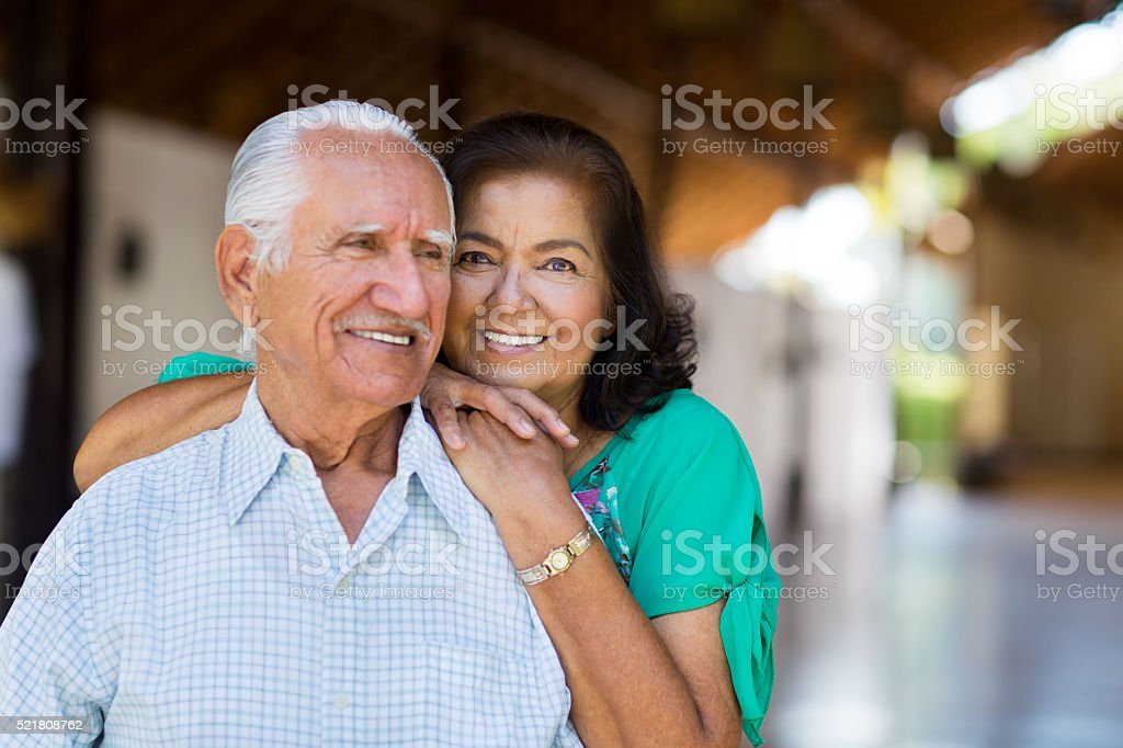 Senior woman placing hands on the shoulder of senior man stock photo