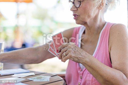 istock Senior woman playing cards 825818324