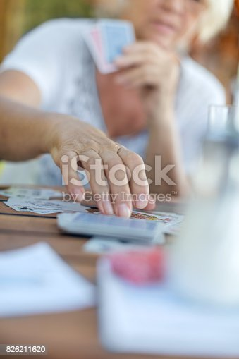 istock Senior woman playing cards 826211620