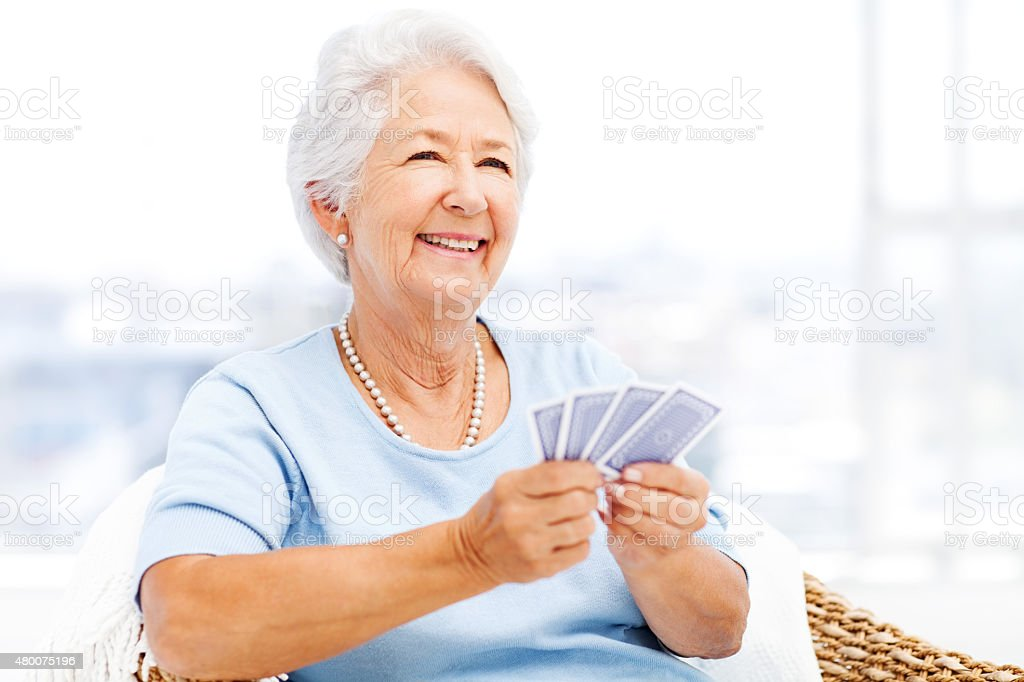 Senior Woman Playing Cards While Looking Away stock photo