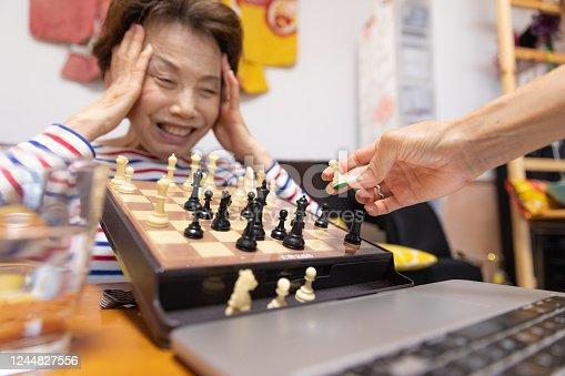 Senior woman playing chess on video call