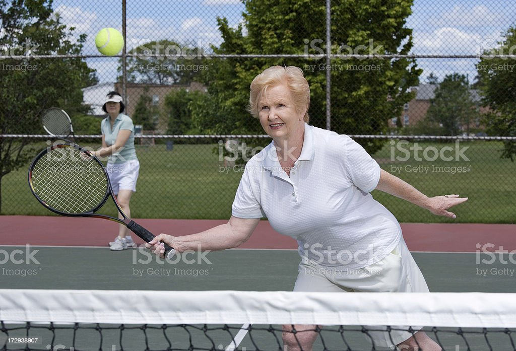 senior woman playing doubles tennis stock photo