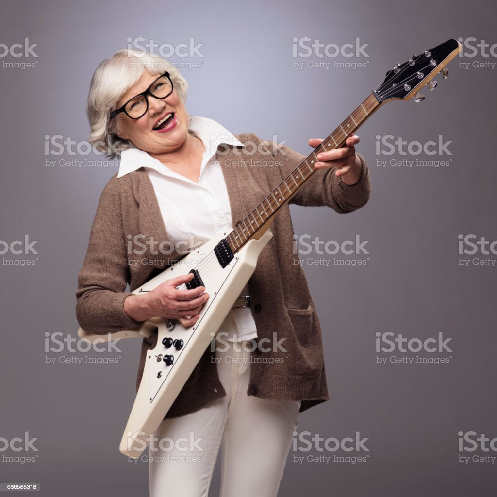 Senior woman playing electric guitar stock photo
