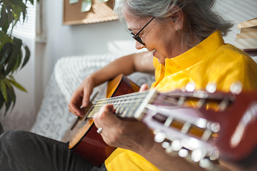 Close up of Senior woman playing guitar ay home