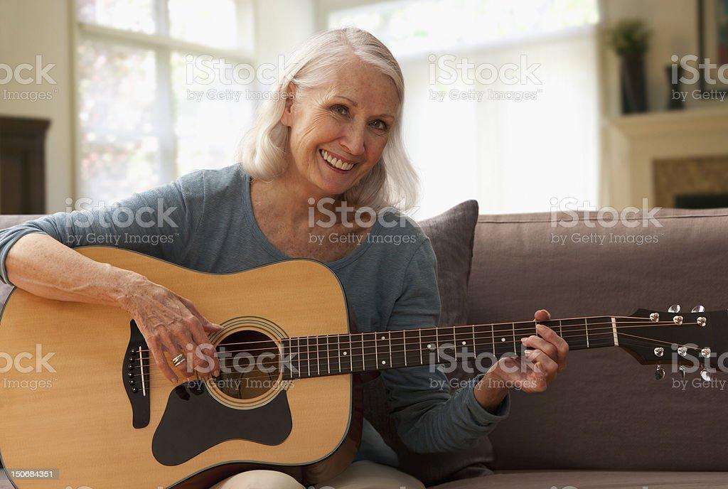 Senior woman playing guitar royalty-free stock photo