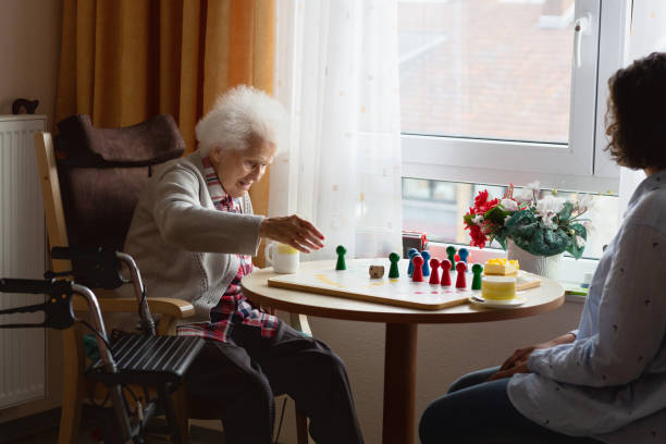 Senior woman playing Ludo game with caregiver stock photo