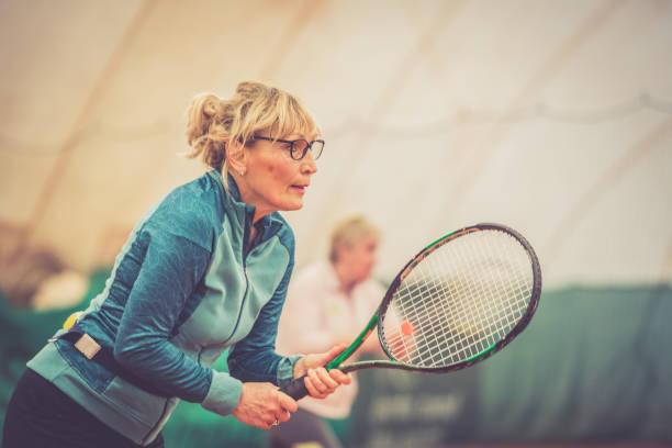 senior woman playing tennis portrait - showus стоковые фото и изображения