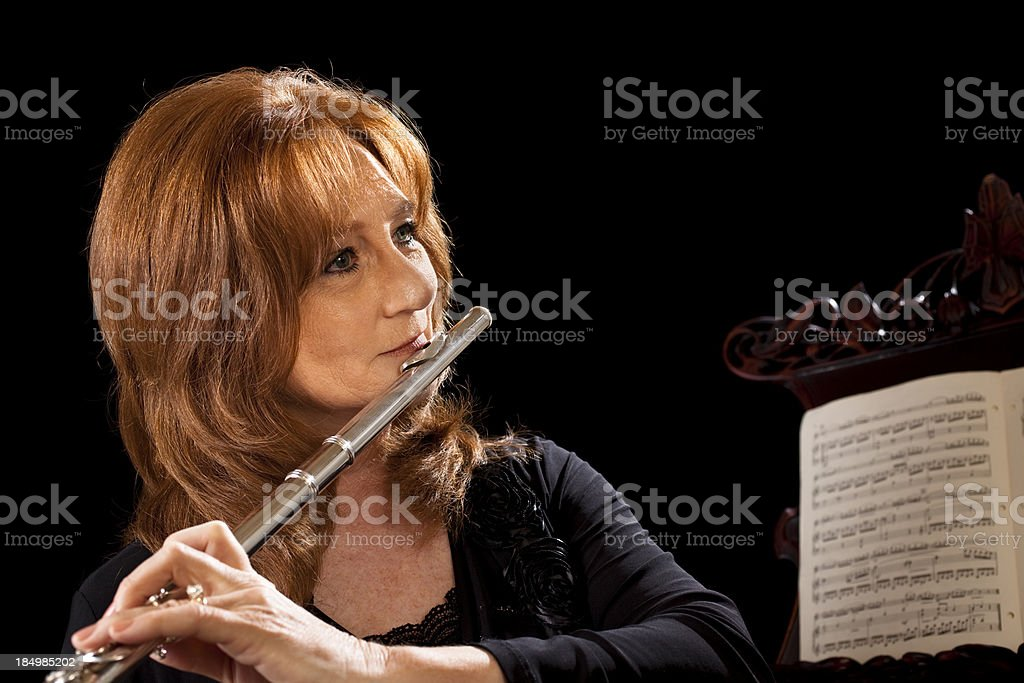 Senior woman playing the flute.  Music and stand. royalty-free stock photo