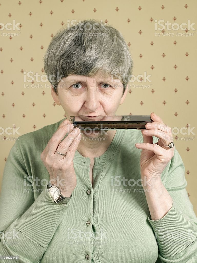 Senior woman playing the harmonica stock photo