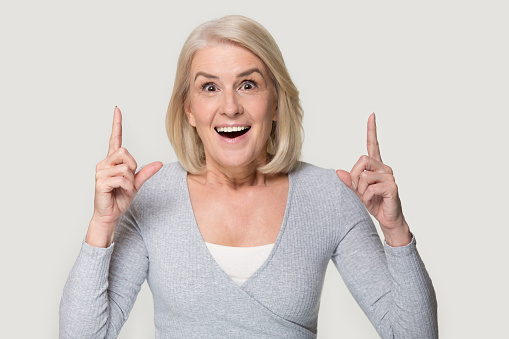 istock Senior woman pointing fingers up feels excited studio head shot 1151796056