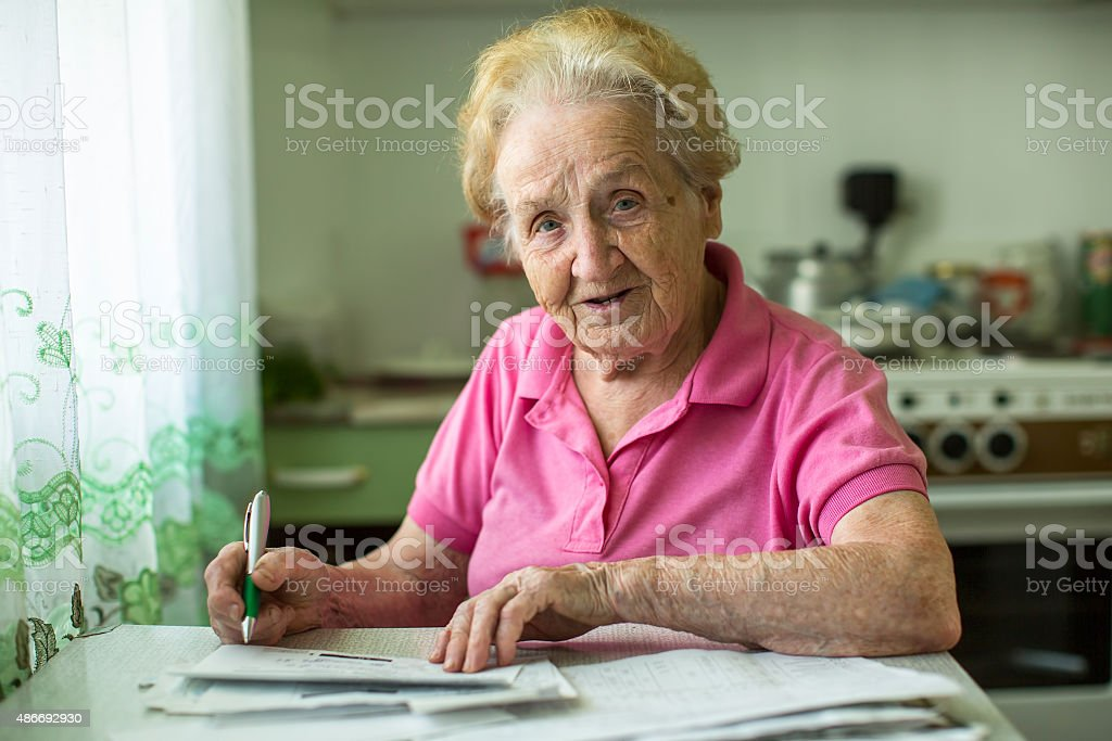 Senior woman populates handle her utility bills notices stock photo