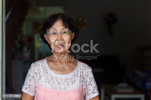 Portrait shot of a confident senior Asian woman standing in front of her house