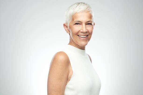 Seniorin posiert vor grauem Hintergrund. – Foto